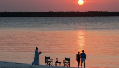 Couple enjoying a sundowner in mnemba Island